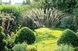 Sprinkler watering lawn of small town garden, June