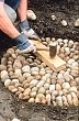 tamping down stone mosaic to form level surface