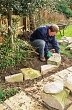 setting first layer of stones in drystone retaining wall