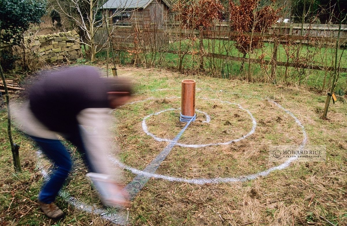 Marking spiral in rough grass ready to plant with crocus bulbs
